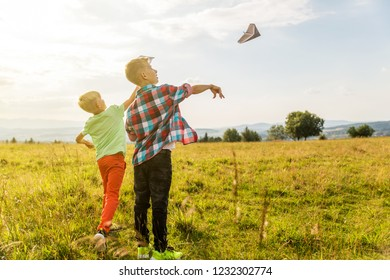 Boys playing with paper airplanes in a meadow