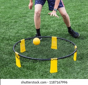 Boys are playing spike ball on a green turf field