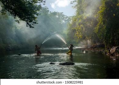 Boys playing splash water at beautiful river in Bogor West Java Indonesia. 04 08 2019