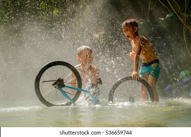 boys playing their bicycle in creek, laughing happily