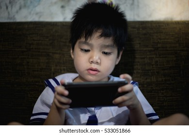 Boys playing video games on telephone.