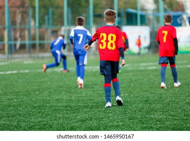 Boys in red and blue sportswear plays  football on field, dribbles ball. Young soccer players with ball on green grass. Training, football, active lifestyle for kids