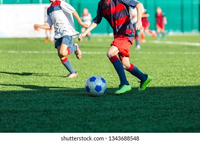 Boys in red blue white sportswear running on soccer field. Young footballers dribble and kick football ball in game. Training, active lifestyle, sport, children activity concept