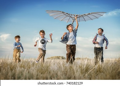 Boys is running with a kite during the day in the field