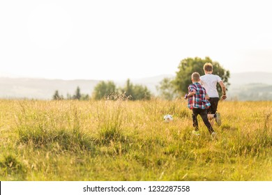 Boys running in the meadow, having fun