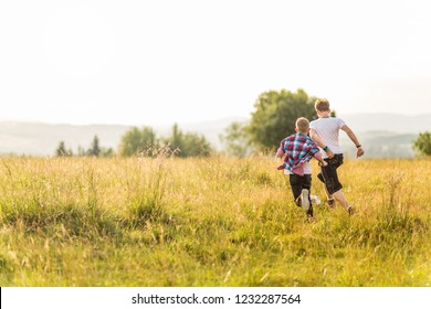 Boys running in the meadow, having fun