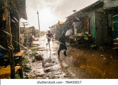 Boys running through african market during rain, Kenya