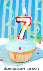 boy's seventh birthday cupcake with blue frosting and  decorative background
