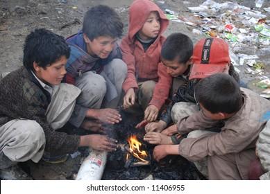 Boys sit around fire