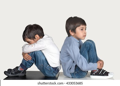 boys sit on a floor a back to a back - have quarreled