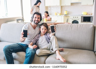 Boys are sitting on sofa and holds phone in hands. They are showing them on camera. Womna and girl are standing in kitchen and cooking.