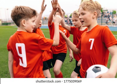 A boys soccer team celebrating a victory. Motivated children sports team rising hands up. Young school football team on the outdoor grass pitch. Happy kids playing sports