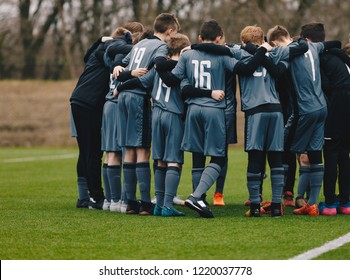 Boys Soccer Team Doing Motivational Pre Game Chant. Young Footballers Standing Together United and Listening Coach Motivational Speech. Kids Sports Team Wearing Grey Soccer Kit and Football Cleats