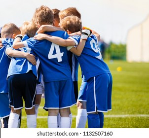Boys sports team with coach. Youth soccer team huddle with coach. Motivation talk, pep talk before the match. Young football soccer players in jersey blue sportswear