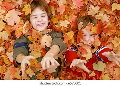 Boys Throwing Fall Leaves