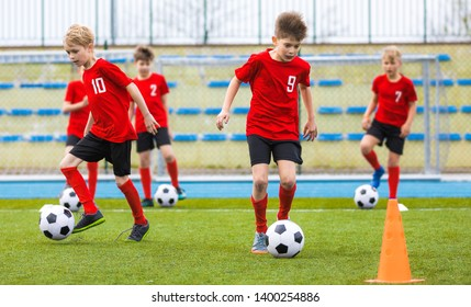 Boys training soccer skills on grass field. Football school class for children