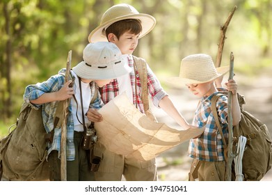 Boys travelers with backpacks studying the route map in a sunny summer day