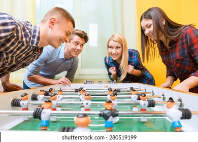 Boys vs girls. Young smiling boy playing air hockey against young Asian girl watching the play while their friends standing near and cheering them up