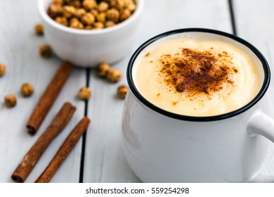 Boza or Bosa with cinnamon and roasted chickpea; Traditional Turkish drink made of millet or corn flour