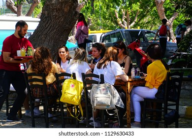 BOZCAADA, TURKEY - APR 28, 2018 - Young Turkish people at lunch at an outdoor restaurant in Bozcaada, Turkey