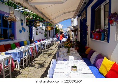 BOZCAADA, TURKEY - APR 28, 2018 - Lunch in red restaurant on a narrow street on the island of Bozcaada, Turkey