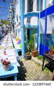 BOZCAADA, TURKEY - APR 28, 2018 - Lunch in blue restaurant on a narrow street on the island of Bozcaada, Turkey