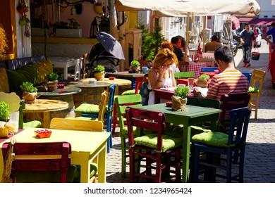 BOZCAADA, TURKEY - APR 28, 2018 - Lunch in  restaurant on a narrow street on the island of Bozcaada, Turkey