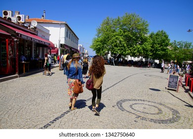 BOZCAADA, TURKEY - APR 28, 2018 - Tourist explore the hotels and restaurants  on the waterfront of  the island of Bozcaada, Turkey