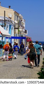 BOZCAADA, TURKEY - APR 28, 2018 - Tourist explore the hotels and restaurants  on the waterfront of  the island of Bozcaada, Turkey