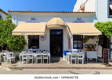 Bozcaada,Turkey-August 21,2019: Exterior of old houses and cafes of Bozcaada in Aegean see.The Island is very populer for tourists
