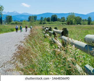 Bozeman, Montana/USA -July 20, 2019 : 4 people walking and biking along a rural gravel path on a sunny summer day with majestic mountains in the distance
