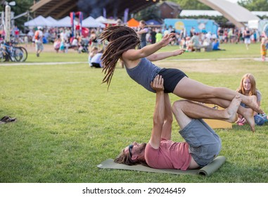 Bozeman, Montana/USA - JUNE 23,2015: A couple practice acrayoga in the park during the summer farmers market. The man is balancing the woman using technique and strength.