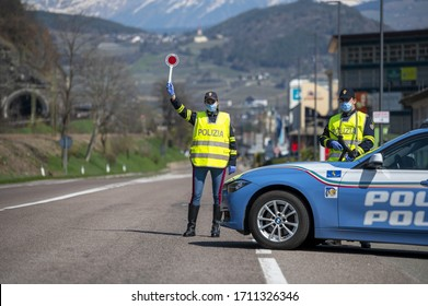 BOZEN, ITALY - APRIL 23, 2020. Italian Police controls on the road. Officers with masks and gloves monitor passing motorists. Street control for the Covid-19 with a policewoman. Police checkpoint.