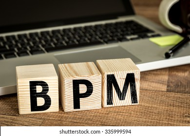 BPM (Business Process Management) written on a wooden cube in a office desk