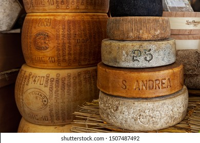 BRA, ITALY - SEPTEMBER 18. 2015: Smoked hard cheese and Parmesan wheels on the stall during traditional International Cheese Market taking place every two years in town of Bra in Piedmont, Italy.