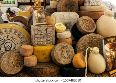 BRA, ITALY - SEPTEMBER 18. 2015: Different types of artisan smoked hard cheese on the stall in traditional International Cheese Market taking place every two years in town of Bra in Piedmont, Italy.