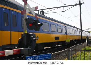 BRABANT (NEAR NIJMEGEN), NETHERLANDS - APRIL 21. 2019: View on coming dutch train at railroad crossing with clothed barrier and red warning light