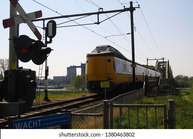 BRABANT (NEAR NIJMEGEN), NETHERLANDS - APRIL 21. 2019: View on coming dutch train at railroad crossing with barrier