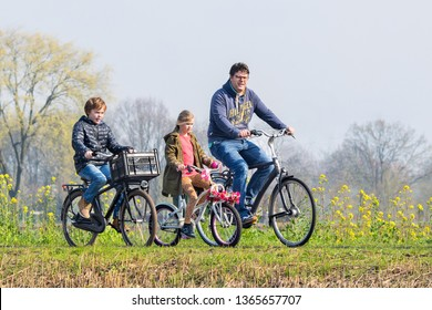 BRABANT-APRIL 7, 2019. A father has a recreational cycle tour with his kids on a spring day. Dutch people love cycle in their bicycle-friendly country with 22 million bikes and 35,000 KM bike paths.
