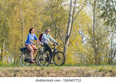 BRABANT-APRIL 7, 2019. Middle aged couple enjoys the spring weather on a bike tour. Dutch people like to cycle in their bicycle-friendly country with 22 million bikes and over 35,000 KM bike paths.