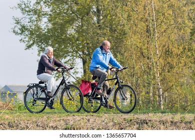 BRABANT-APRIL 7, 2019. A senior couple enjoys the spring weather on a bike tour. Dutch people like to cycle in their bicycle-friendly country with 22 million bikes and over 35,000 KM bike paths.