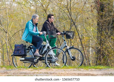 BRABANT-APRIL 7, 2019. Two elderly women enjoys the spring weather on a bike tour. Dutch people like to cycle in their bicycle-friendly country with 22 million bikes and over 35,000 KM bike paths.