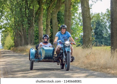 BRABANT-NETHERLANDS-JULY 16, 2018. Cheerful couple on classic motor with sidecar. The Netherlands has a large group of enthusiasts riding old fashion bikes, feeling the spirit of iconic machines.