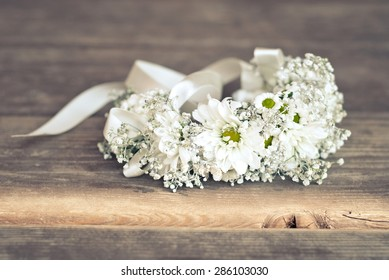 Bracelet with chamomile flowers on the wooden floor