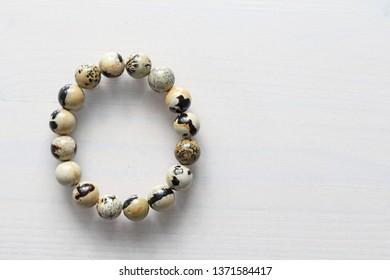 Bracelet from a natural landscape jasper. Bracelet made of natural stones on a white background. Jewelry made of natural stones. Copy space for your text.