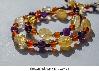 Bracelet and necklace hand made using colourful semi-precious gemstone beads including yellow citrine, purple amethyst and orange carnelian.