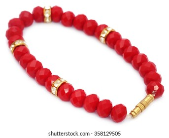 Bracelet of red beads over white background
