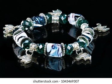 the bracelet with stones and figures has been photographed on a black background in studio