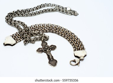 Bracelets, chains and crosses of silver on a white background