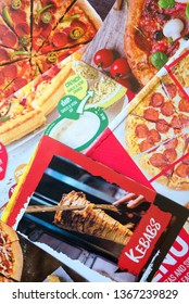 Bracknell, England - April 11, 2019: Sample of fast food leaflets and flyers delivered to a private address in Bracknell, England to advertise local services and business